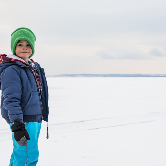 """""""A young boy walking on a frozen lake while ice fishing during a winter family..."""" stock image"""