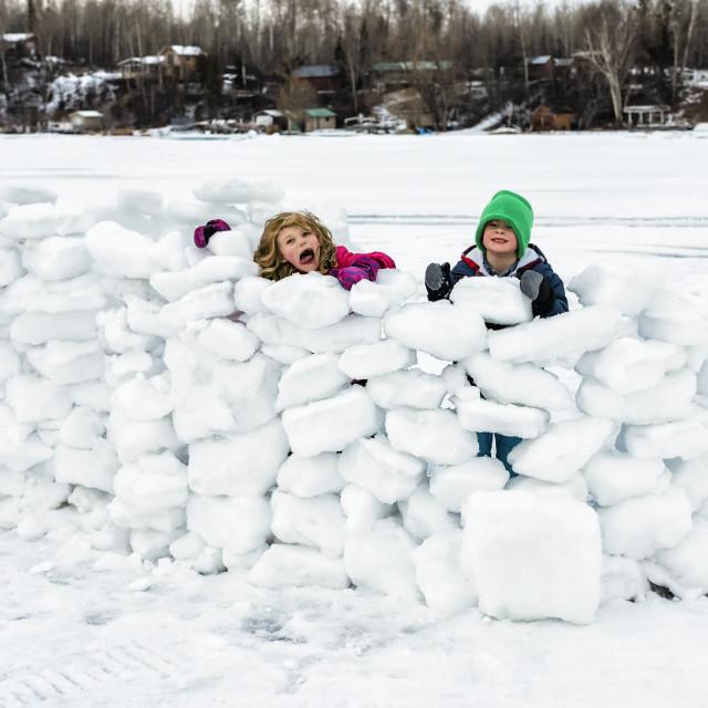 """Children playing in a snow fort on frozen Lake Wabamun; Wabamun, Alberta, Canada"" stock image"