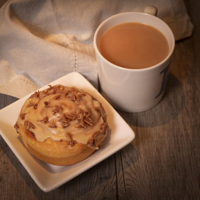 """""""Mug of tea with a sweet bun"""" stock image"""