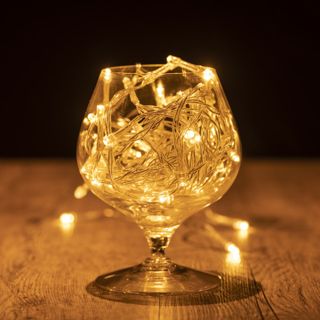 """""""brandy glass with fairy lights on a wooden table"""" stock image"""