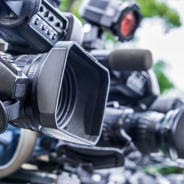 """Professional tv cameras on tripods recording social event"" stock image"