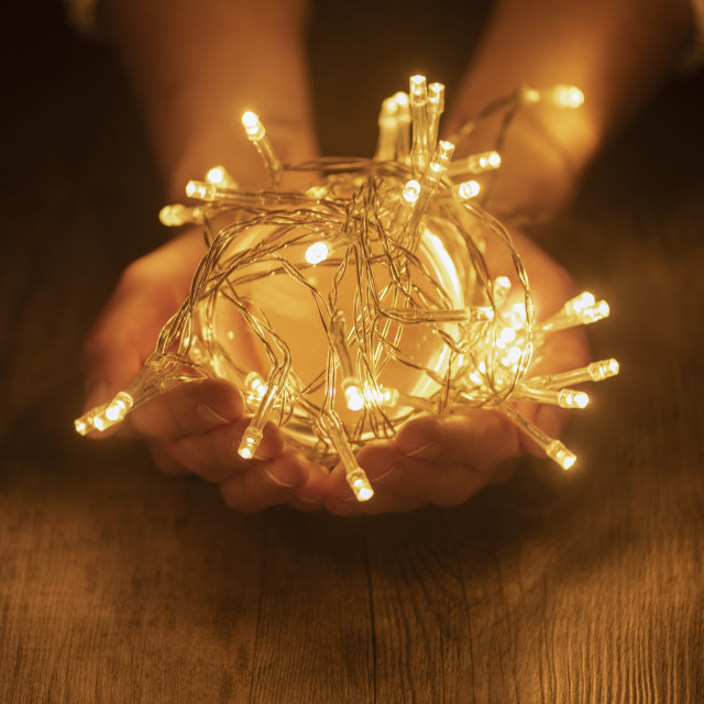 """""""Hands holding a ball of fairy lights"""" stock image"""