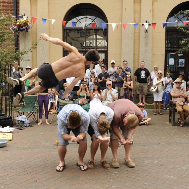 """Dan the acrobat leaps over three volunteers."" stock image"