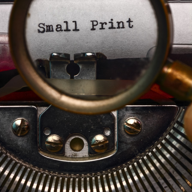 """""""Vintage typewriter with the words small print printed on a letter and a mans hand holding a magnifying glass"""" stock image"""