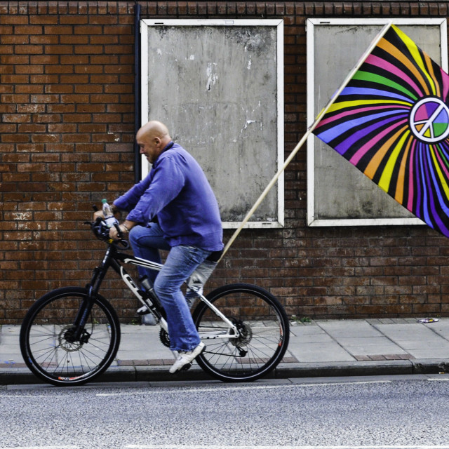 """""""Peace protester with flag on a bike"""" stock image"""