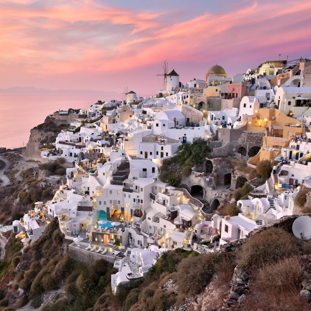 """""""Oia Village in Cycladic Architecture style in Santorini, Greece during a pink sunset."""" stock image"""