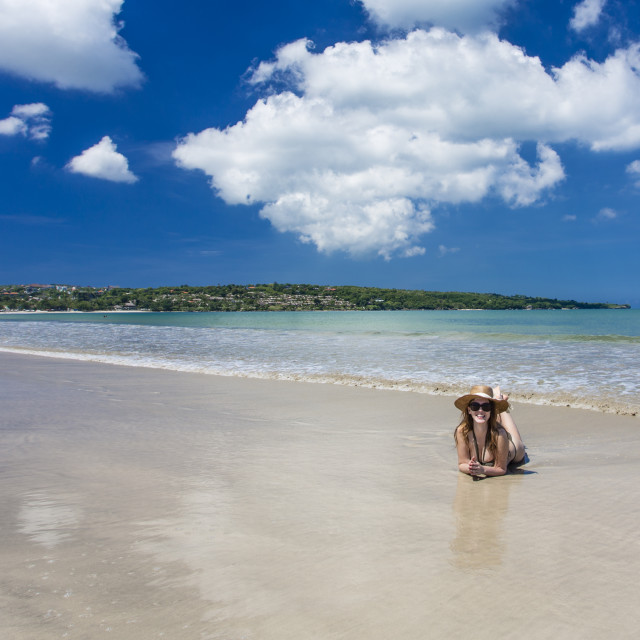 """Woman laying at Jimbaran Beach, Bali"" stock image"