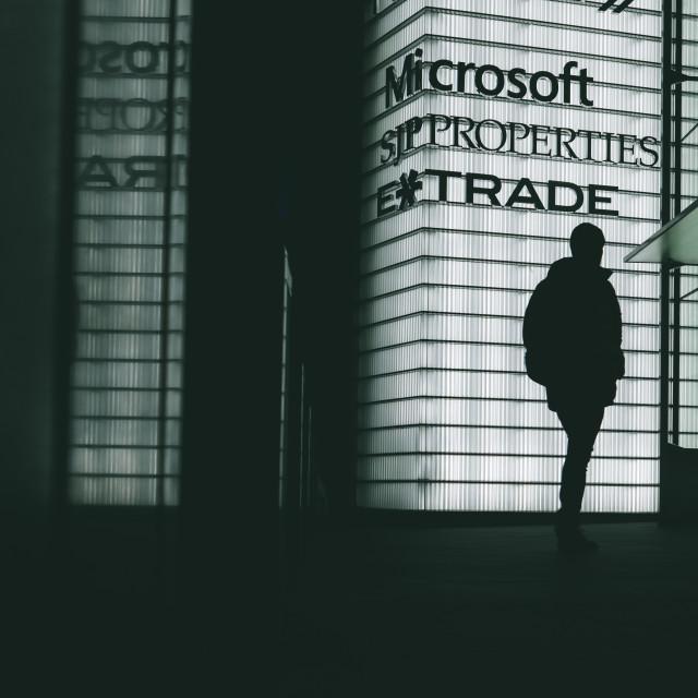 """Dark silhouette of man walking by Microsoft building at night"" stock image"