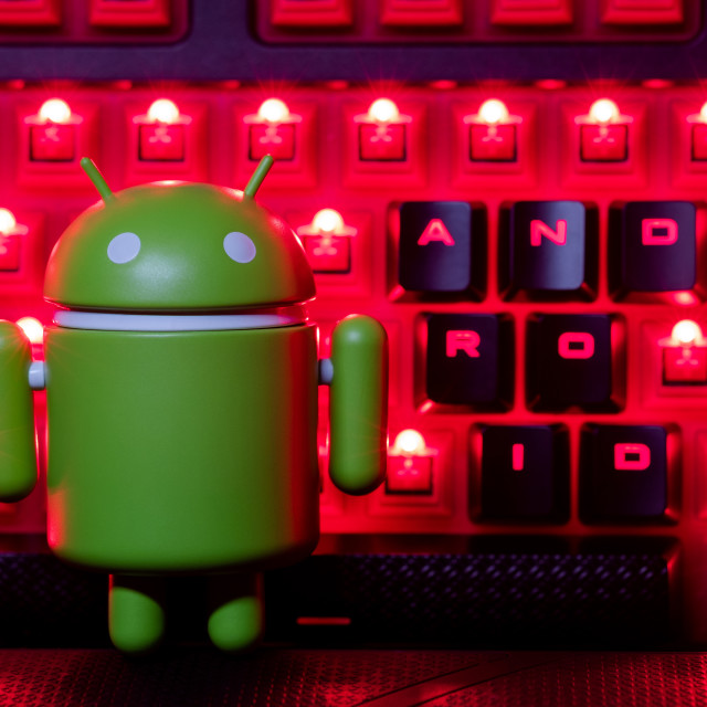 """Google Android figure in front of illuminated keyboard"" stock image"