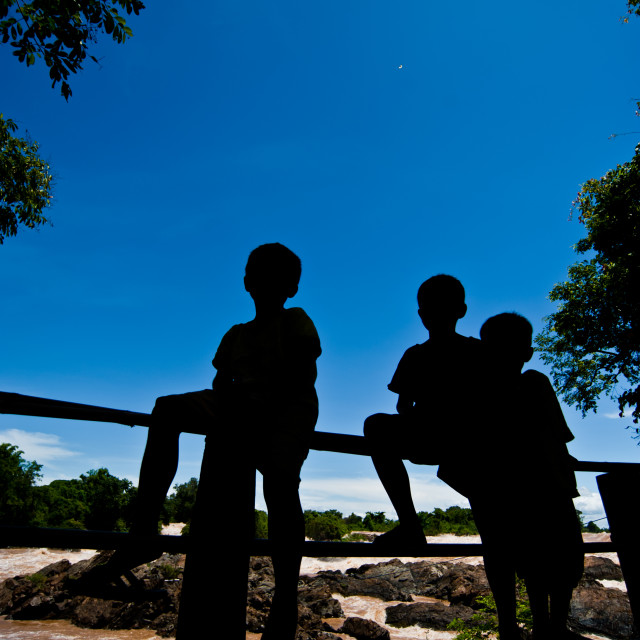 """""""Silhouette Little boy sitting on a fence at Khone Phapheng water"""" stock image"""
