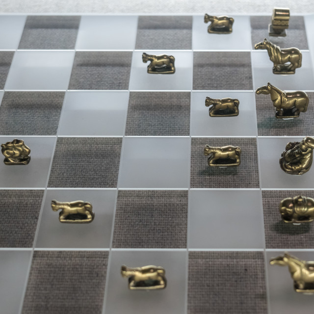 """""""Cast metal chess men on glass board"""" stock image"""
