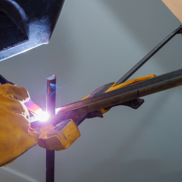 """""""A worker with gloves is welding some railings."""" stock image"""