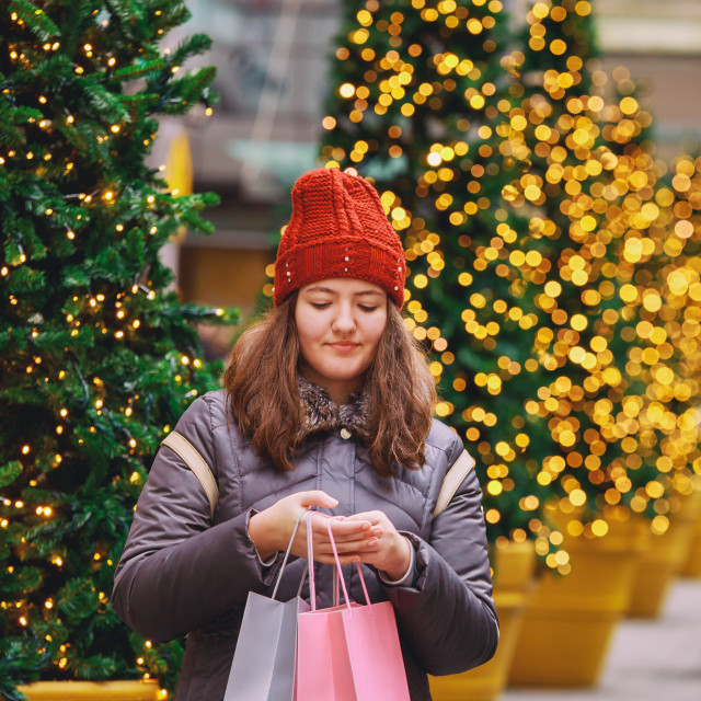 """""""Young happy girl with shopping bags walking on street, colorful lights bokeh..."""" stock image"""