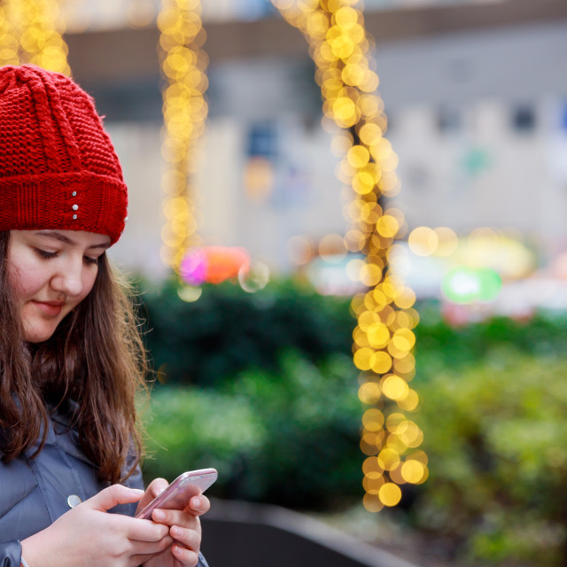 """""""beautiful young girl holding smart phone on a background with bokeh lights"""" stock image"""