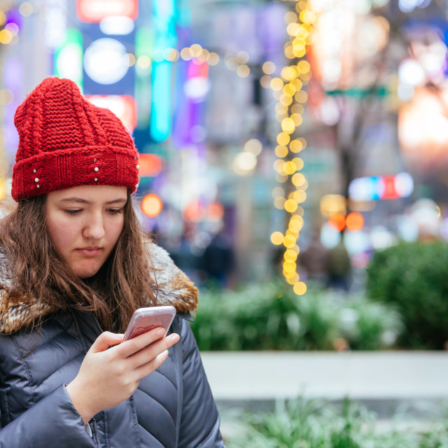 """""""Girl walking and texting on her smartphone"""" stock image"""