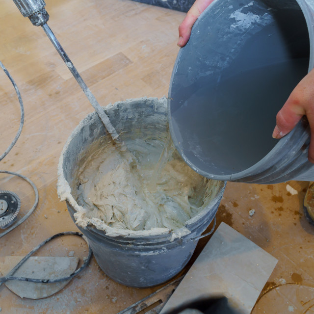 """""""Cement mix tile adhesive in a bucket for tiling using an electric drill"""" stock image"""