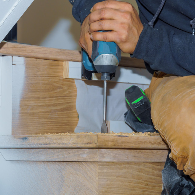 """""""Man screws stairs with drill in park"""" stock image"""