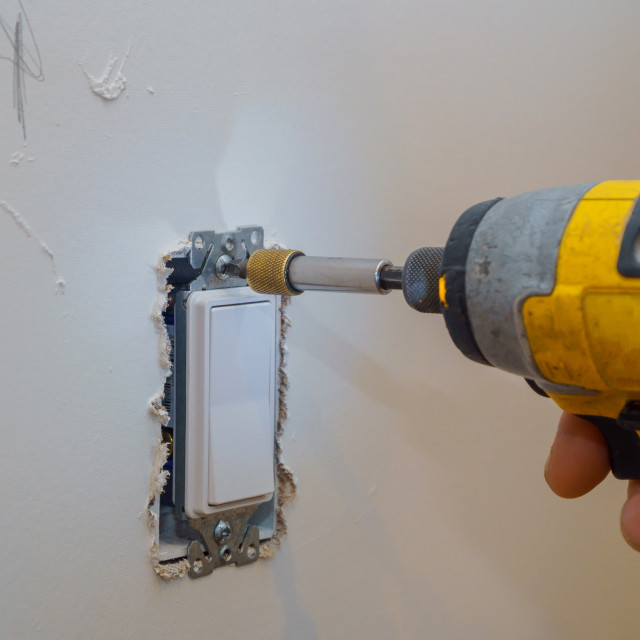 """""""Tightening a Screw on an Electrical Outlet"""" stock image"""