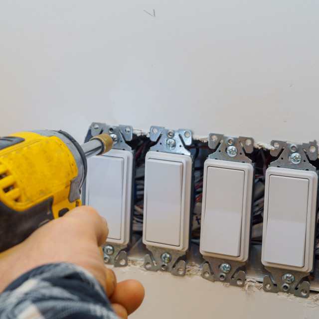 """""""Preparing to install an electrical outlet, checking the fastening of the screws"""" stock image"""