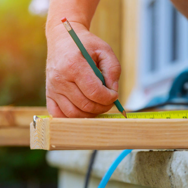 """""""Contractor writes a pencil on the wood beam"""" stock image"""