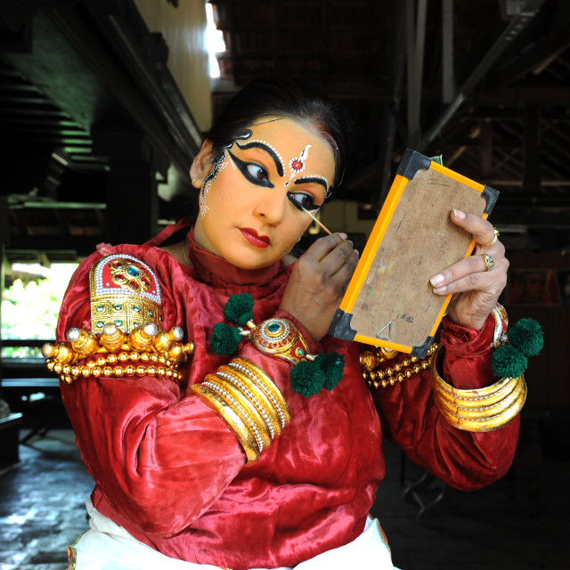 """""""Performer carefully applying make-up with bamboo stick for a Kathakali dance..."""" stock image"""