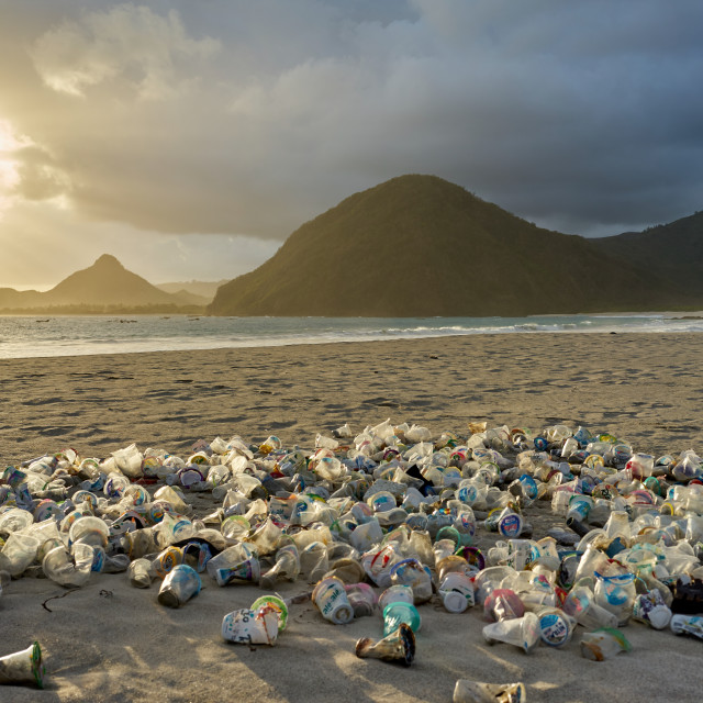 """""""Pile of plastic rubbish dumped on the sand at sunset on Selong Belanak Beach..."""" stock image"""