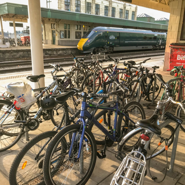"""Commuters' bicycles secured to bike racks at Cardiff Central station."" stock image"