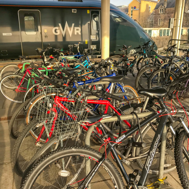"""""""Commuters' bicycles secured to bike racks at Cardiff Central station"""" stock image"""