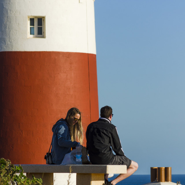"""Two young tourists sitting on bench next to lighthouse, Gibraltar"" stock image"
