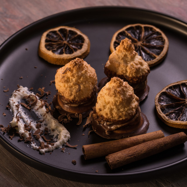 """""""Few pieces of baked sweets on dark plate with orange rings"""" stock image"""