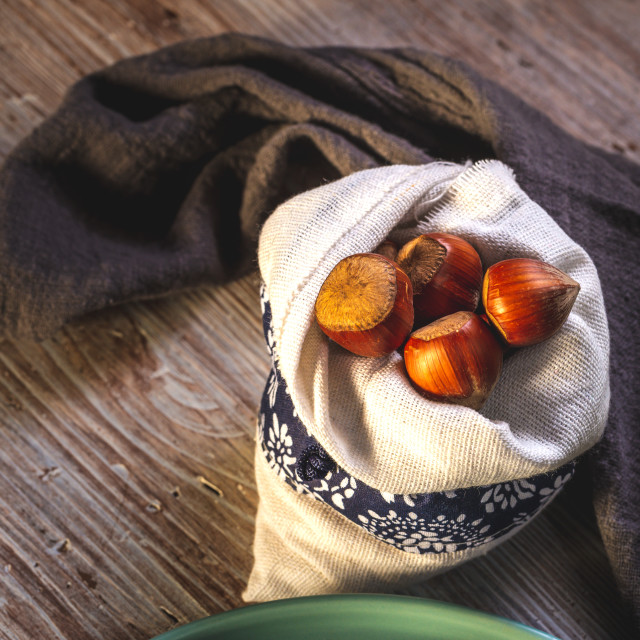 """""""Several hazelnuts in white bag placed on wooden board"""" stock image"""