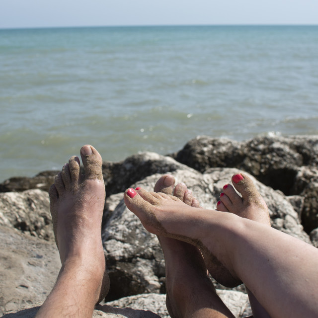 """""""stony coast by the sea with feet of tourists"""" stock image"""