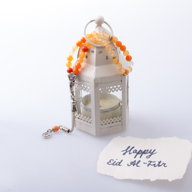 """""""the word EID EL FITR on torn paper beside lantern and prying beads"""" stock image"""