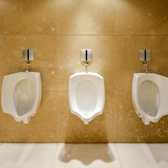 """""""A row of urinals in tiled wall in a public restroom"""" stock image"""