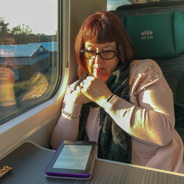 """Person reading an e-reader in the first class carriage of an inter city train"" stock image"