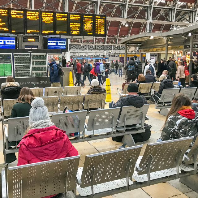 """People sitting down on the concourse of London Paddington Station"" stock image"