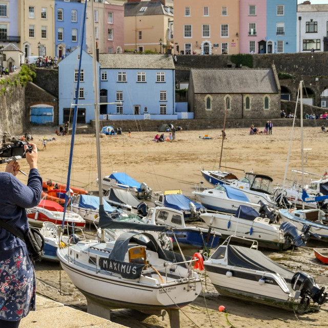 """""""Person taking a photograph of the harbour in Tenby, West Wales"""" stock image"""
