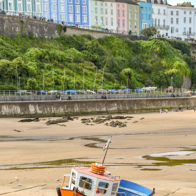 """""""Small fishing boat at low tide in Tenby, West Wales."""" stock image"""