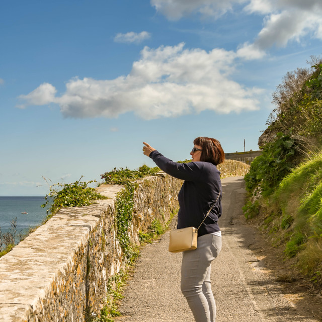 """""""Person in Tenby, West Wales pointing out something of interest."""" stock image"""