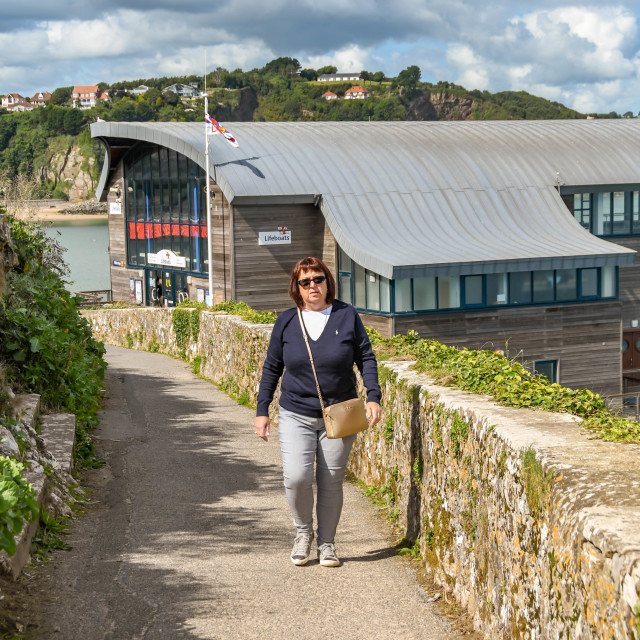 """""""Person walking the coastal footpath in Tenby, West Wales."""" stock image"""