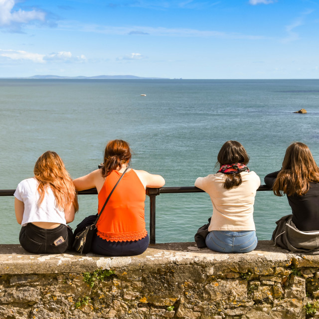 """""""Four young people sitting on a wall in Tenby, West Wales."""" stock image"""