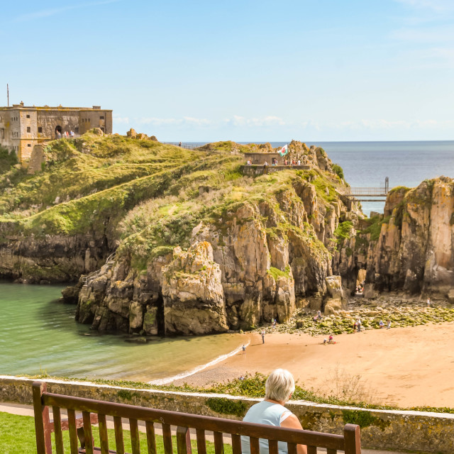 """""""Person sitting on a wooden bench in Tenby, West Wales."""" stock image"""