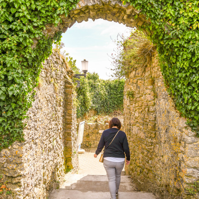 """""""Person walking through a stone archway in Tenby, West Wales."""" stock image"""