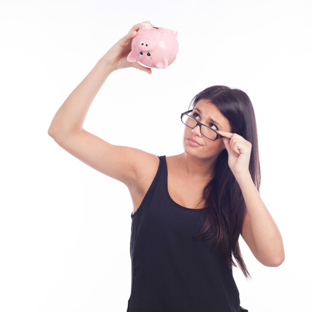 """Young woman worried with a piggy bank"" stock image"