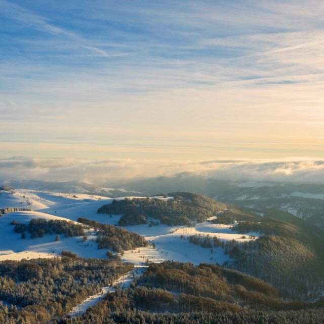"""""""Aerial view of a gold sunset over winter snow."""" stock image"""