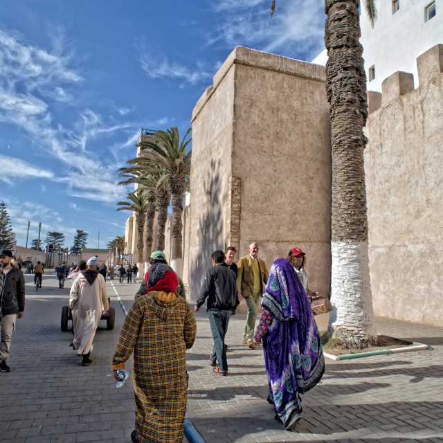 """People and palm trees - sunny street in Essaouira, Morocco"" stock image"
