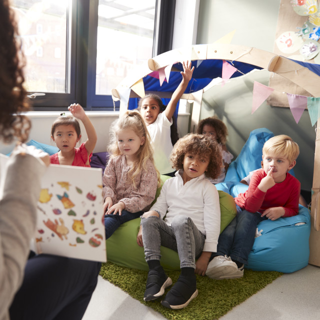 """""""Female infant school teacher sitting on a chair showing a book to a group of..."""" stock image"""