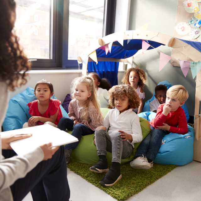 """""""Female infant school teacher sitting on a chair reading a book to a group of..."""" stock image"""