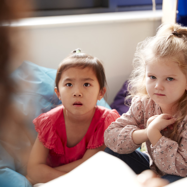 """""""Two infant school girls sitting on bean bags in a comfortable corner of the..."""" stock image"""