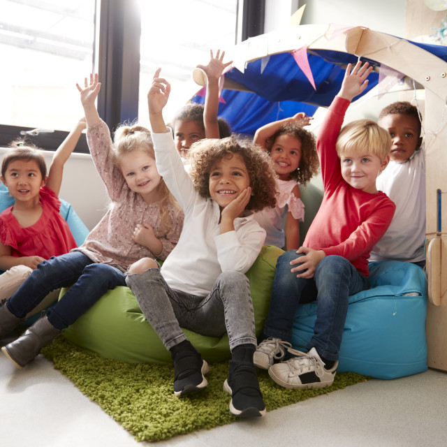 """""""A multi-ethnic group of infant school children sitting on bean bags in a..."""" stock image"""